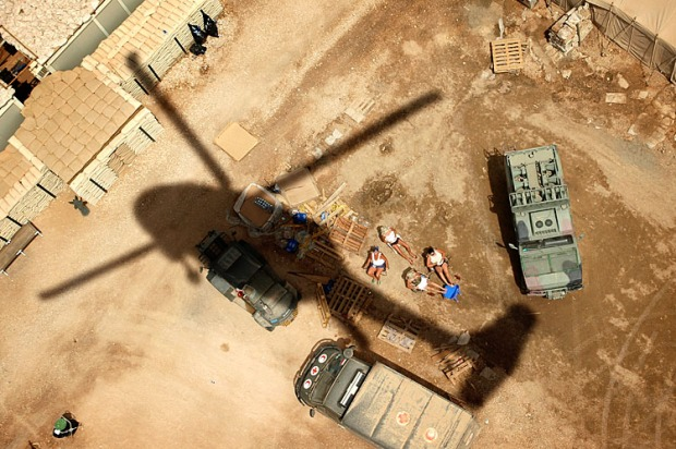 A Black Hawk helicopter carring an American General momentarily blocks the sun of a group of Polish soldiers tanning themselves on a base in Karbala, Iraq on May 3, 2004. The American military were forced to fight for control of Karbala after Muqtada al-Sadr's Mahdi army easily over whelmed the unwilling coalition partner, Poland.