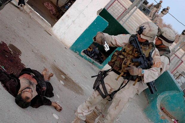 An American military policemen photographs a dead Mahdi Army fighter in Karbala on May 6, 2004. The insurgency in Iraq is rarely seen, usually ducking in and out of vision of the soldiers, and when one is captured or killed the soldiers are curious to see the human face of their enemy.