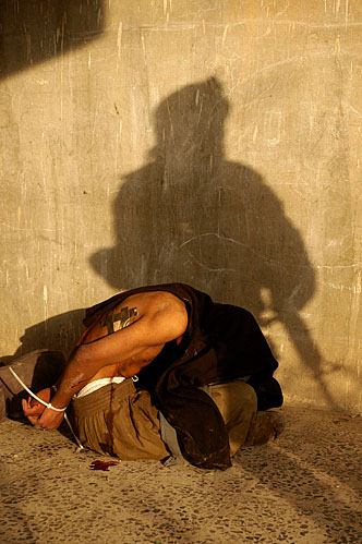 """Marines from Bravo company, 1st Battalion, 8th Marine Regiment detain an insurgent after they shot him and his two comrades in the neighborhood nicknamed """"Queens"""" during the battle for Falluja, Iraq on November 13, 2004. The insurgent claimed to be a student. The marines responded, """"Yeah, right, University of Jihad, motherfucker."""" Image reproduced courtesy of Ashley Gilbertson"""